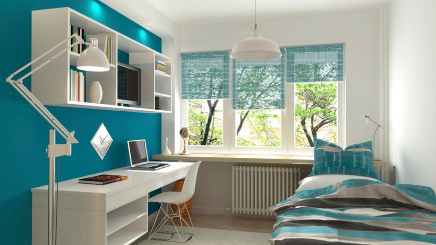 With clean white walls and desk area, the bold blue accent wall helps to balance out the color scheme. Transparent curtains and bedding helps with this as well. A shelving unit above the desk space provides for extra storage and decoration. This space has a dorm room feel is is perfect for a single person.