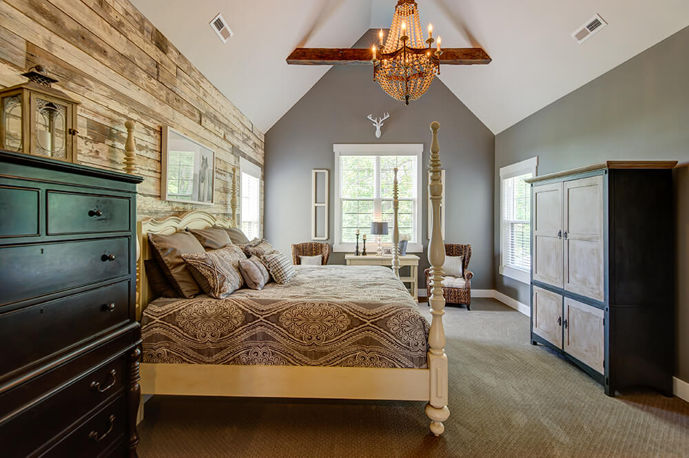 A very attractive primary bedroom featuring gray walls and vaulted ceiling lighted by a glamorous chandelier.
