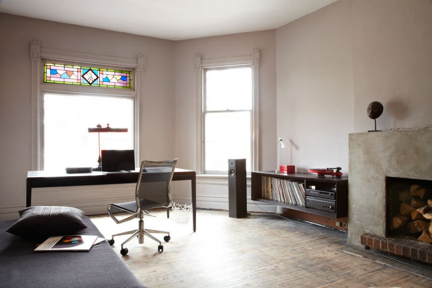 This studio apartment space includes a solid stone fireplace, and fading hardwood floors. There is an entertainment center to the left of the fireplace, and a desk/workspace before the windows. The section of stained glass above the large window gives the room character.
