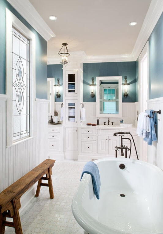 This bright bathroom features a free standing tub, with a large section of cabinetry around the countertop and sink area. The stained glass window breaks up some of the natural lighting, and adds a unique design element to the room.