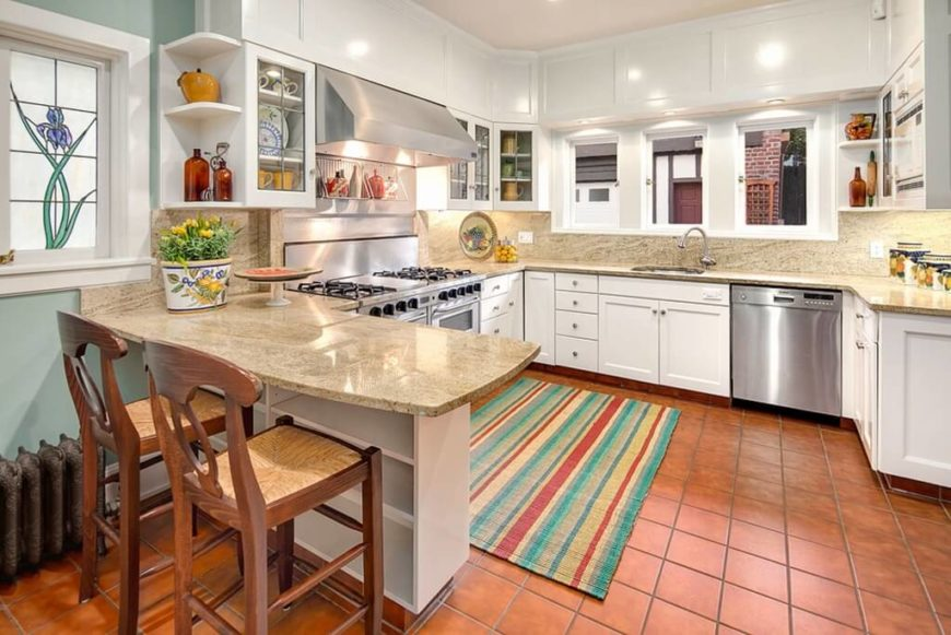 There is rusty brown tile covering the floor in this kitchen, with white cabinetry and beige textured countertops. Next to the eat in extension, there is a stained glass window with a flower design.