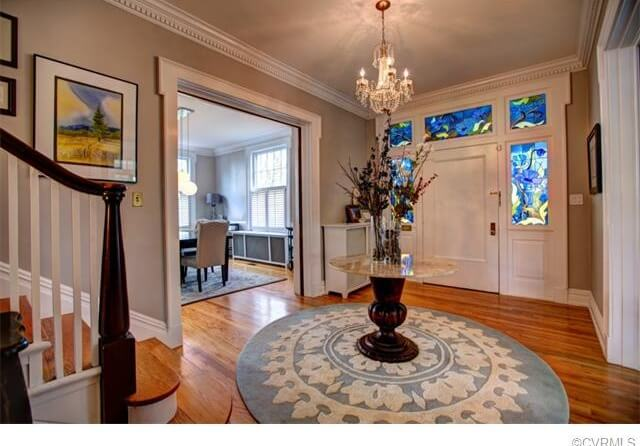 This entryway features a circular area rug, with a decorative table centered on top of it. The door features a stained glass surrounding, which adds rich color to the space and accents the room.