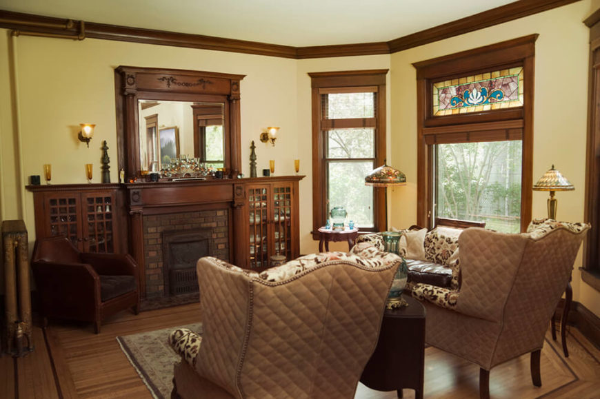 This living room features large upholstered chairs, and an impressive fireplace and mantle. The dark stained wood trim around the windows helps to set a general tone for the space. There is a small section of stained glass above the largest window, providing an colorful accent for this room.