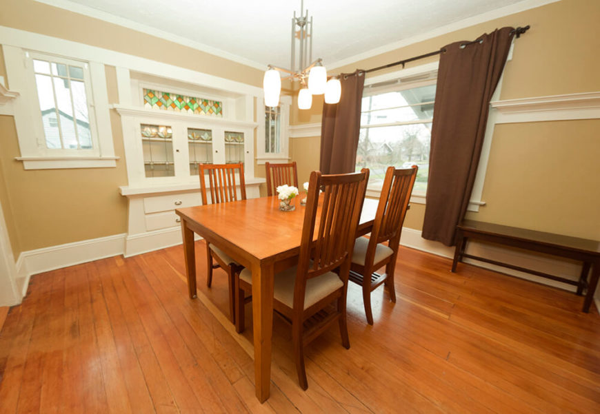 This is a large room, with thick white trim around the entire room, including the windows and built in china cabinet. Featured on the cabinet is a large pane of stained glass across the top, with flower like designs below that compliment the design as a whole.