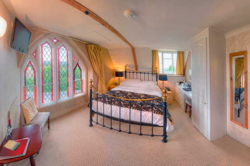 This bedroom has a light beige carpet, with a metal bed frame and a golden yellow curtains around the windows. There is a single wooden rafter featured on the ceiling that acts as a defining line for the division of space in the bedroom.