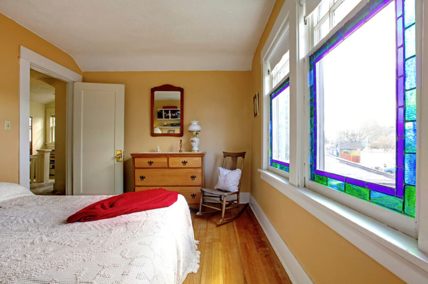 This bedroom has golden yellow walls framed by white trim. There are two large windows with stained glass perimeters. This adds a splash of color to the room and accents the space nicely.