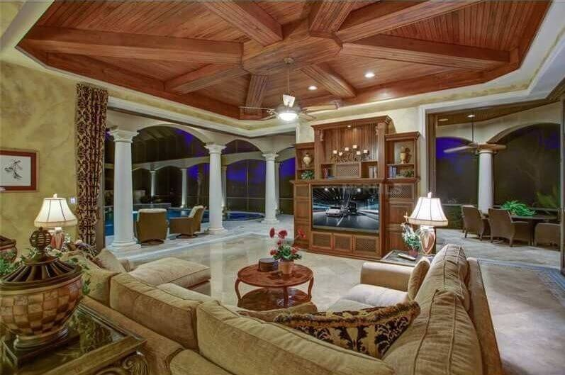 This living space has a high vaulted ceiling, with richly stained wooden rafters spanning out from the center. An entertainment center is featured across from a large upholstered sofa, which wraps around a small coffee table.