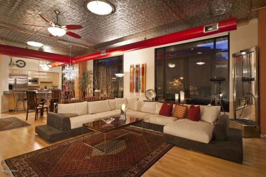 This living room is spacious, and opens up into the kitchen/dining room. The ceiling is made of tin tile materials, which reflects light and makes the space unique. Intricate patterns on both the ceiling and area rug suggest an eastern theme.