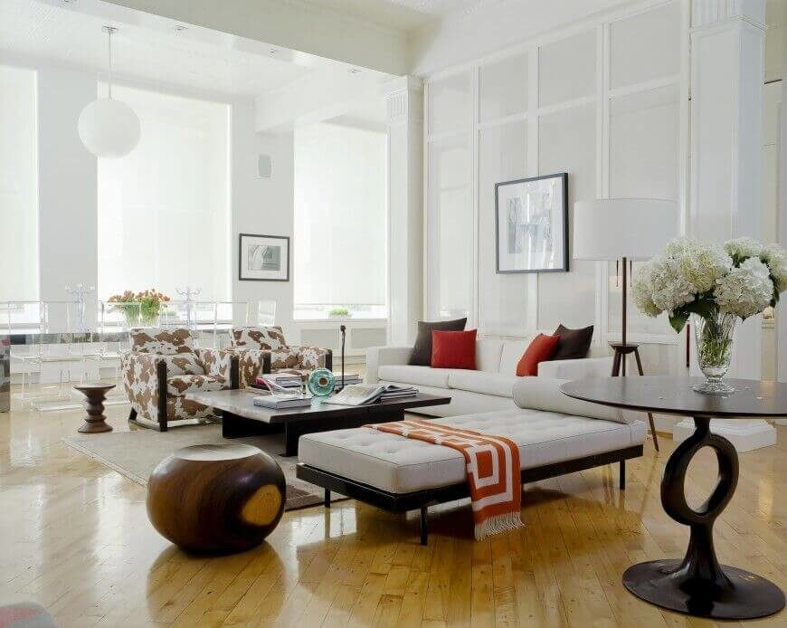 A bright and spacious living room, with large windows that allow natural light to flood into the room. The light reflects off of the high gloss hardwood floor, white the unique side tables and other decorations add character to the space.