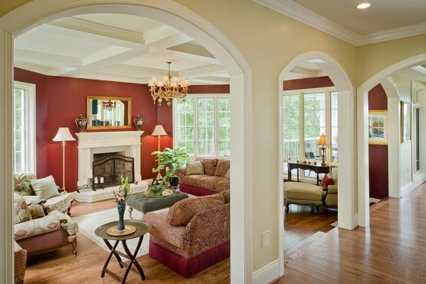 A living space with large hallway openings, separated by small sections of wall. The sofa has an intricate pattern, and the red color matches that of the interior walls.