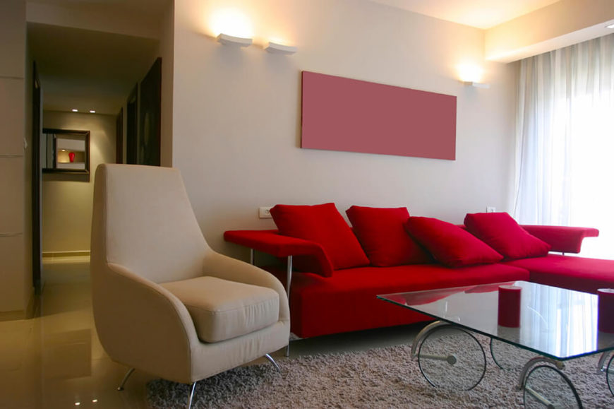 This living room is set upon a glossy finished tile floor, with a large plush area rug drawing all the furniture together. The red couch is vibrant and contrasts the beige colors in the rest of the space.