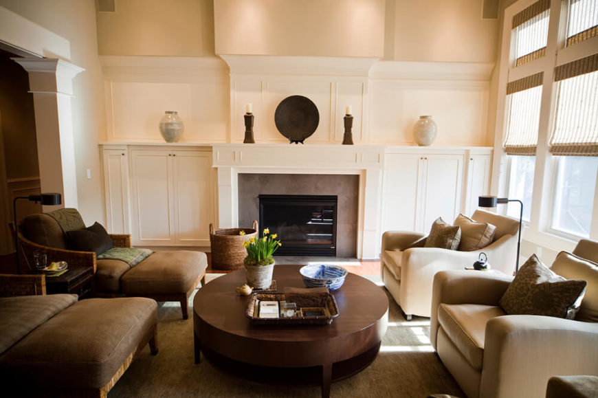 This living room features beige walls and some darker furniture to help give the room depth. Stuffed lounge chairs surround a large wooden coffee table, while natural light from the windows helps to illuminate the room.