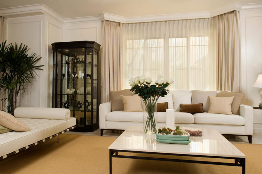 The large tan area rug sits upon a glossed marble floor, and helps to draw the furniture in the room together. The corner holds a china cabinet, with a black frame that heavily contrasts the lighter colors in the room.