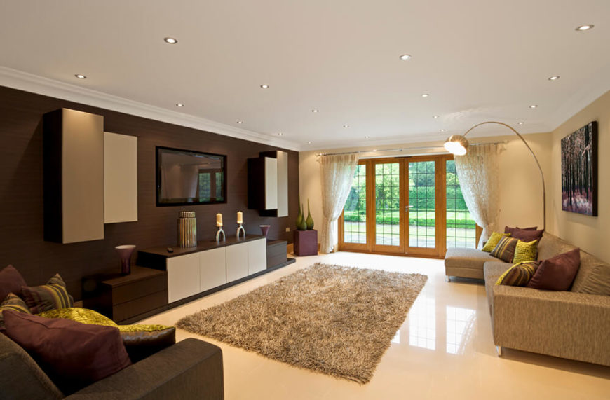 A spacious living room, with contrasting colors on the walls. The wall behind the entertainment center is a dark brown, accented by lighter cabinets around and below the TV. There is a large plush carpet which is centered in front of the TV, drawing the room together.
