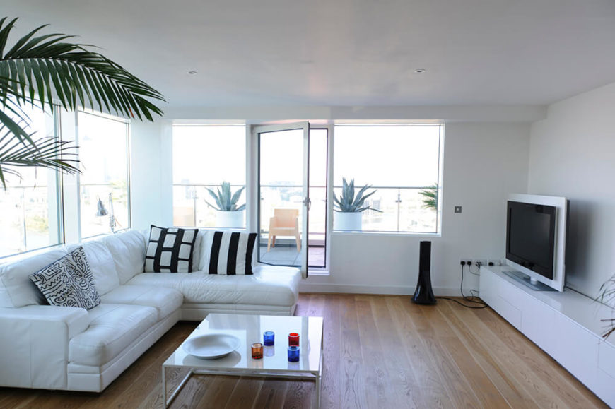 A living room with light hardwood floors, and a mostly white color scheme. The black striped accent pillows provide some variation, along with the multicolored decorations on the coffee table. The large windows let natural light fill the room.