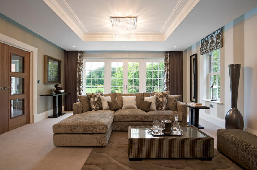 This living room features dark brown tones, balanced by white wood trim along the walls, as well as a white vaulted ceiling with a brightly shining light fixture.