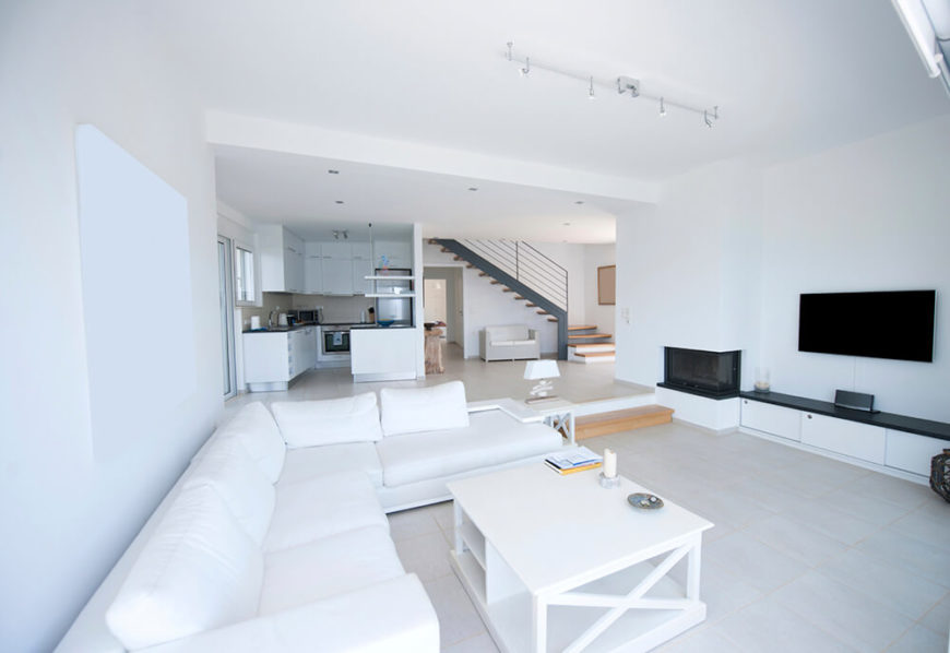 The white theme in this living room helps to make any other color stand out. The black television and bench below are accented, as they are pitch black and surrounded by white. There is also a small golden wood step leading up to the kitchen.