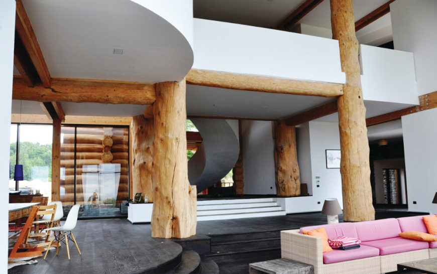 Moving inside, we arrive at the central open space of the home, the main intersection between the living room, dining area, kitchen, and passages to the private bedroom areas. Massive log columns stand supporting the structure at center.