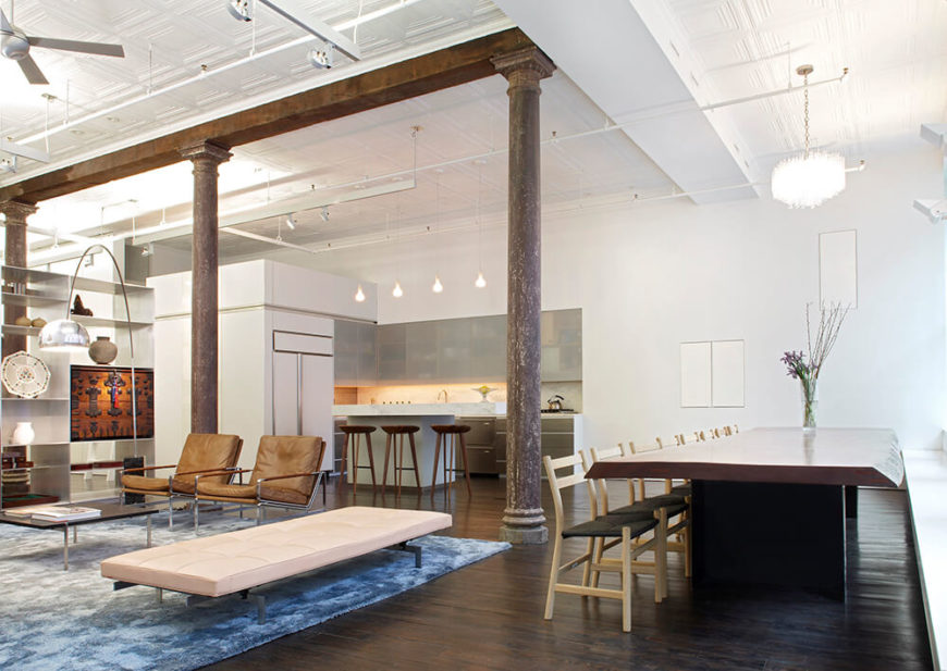 White walls and ceilings help to reflect the light from the windows around the rest of the space. The wood floors are the original industrial floors stained dark to offset the white additions to the space. They kept the stain to a similar color to the pillars that run the length of the loft.