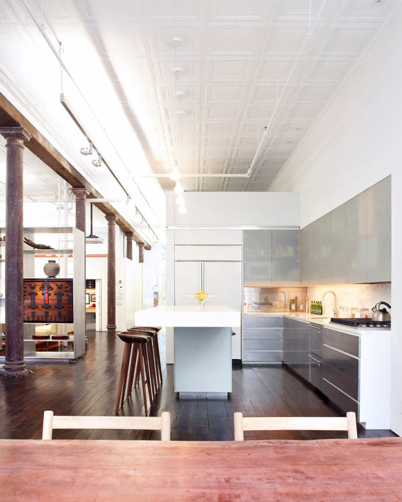 The center island is a steel support structure wrapped in acrylic to support the marble slab on top that matches the marble steps deeper in the house. Overlooking the kitchen is a lofted sleeping area, accessed by the ladder seen in previous images.