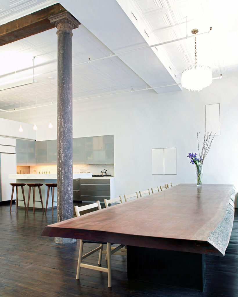 """The dining table is a feature piece of the loft. This custom piece was designed by Slade Architects and fabricated by Inform. Crafted from one single piece of Makore wood, the table measures 19' long and 48"""" wide and runs the length of the east wall of windows."""