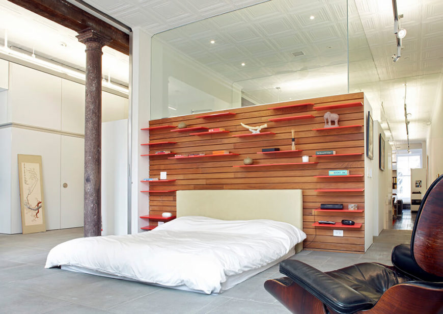 The primary bedroom is the final area of the house, taking up the entire west end of the apartment. The accent wall behind the bed is covered in teak slat wall; bright orange shelves have been inserted into the wall and can be moved as the owner sees fit. The accent wall shares a wall with the primary bathroom.