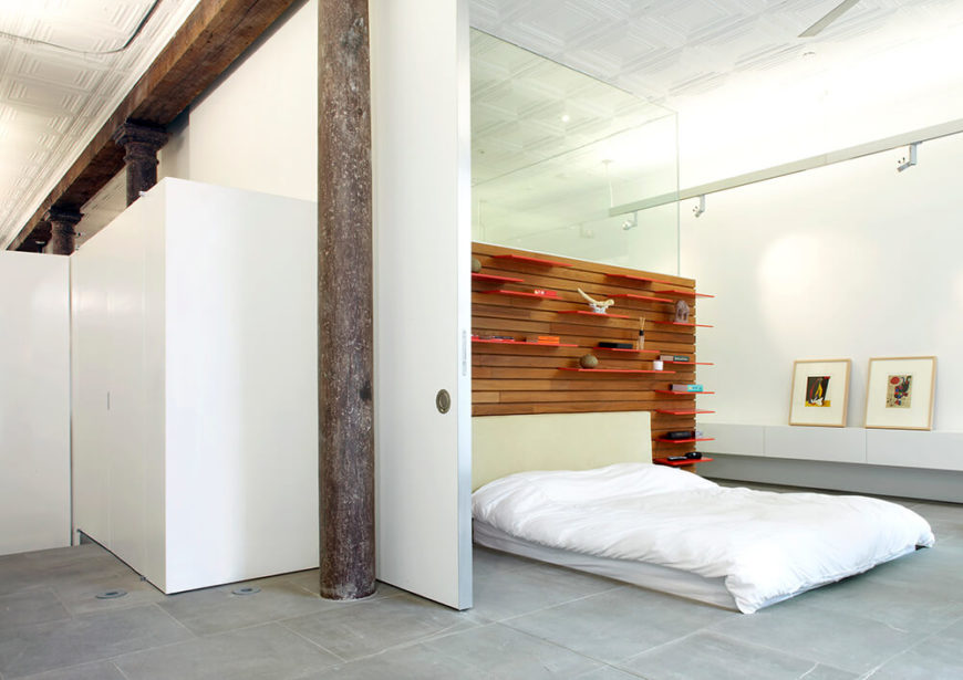 The full-height sliding wall seen behind the pillar divides the primary bedroom into two sleep areas instead of one huge room. This effectively creates a guest room, complete with access to the guest bathroom and the rest of the house without disturbing anyone in the primary bedroom.