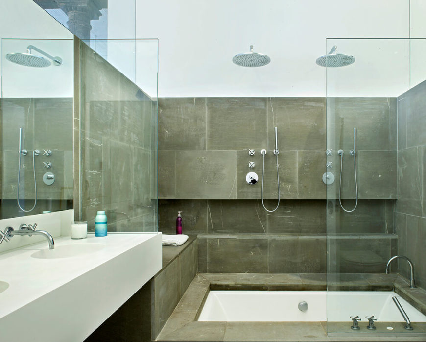 The teak floor hides a surprisingly large soaking tub, making this bathroom versatile and lacking of nothing. The sleek design of the silver fixtures carries the colors of other areas of the house into this room too.