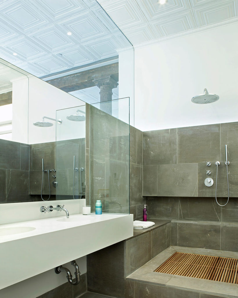 Glass panels reach up to the ceiling in the primary bathroom, giving the room privacy without sacrificing the open concept and reflected light. The white dual vanity sink balance the dark grey of the slate tiles. The slate clad his-and-hers shower features a removable teak slat floor.