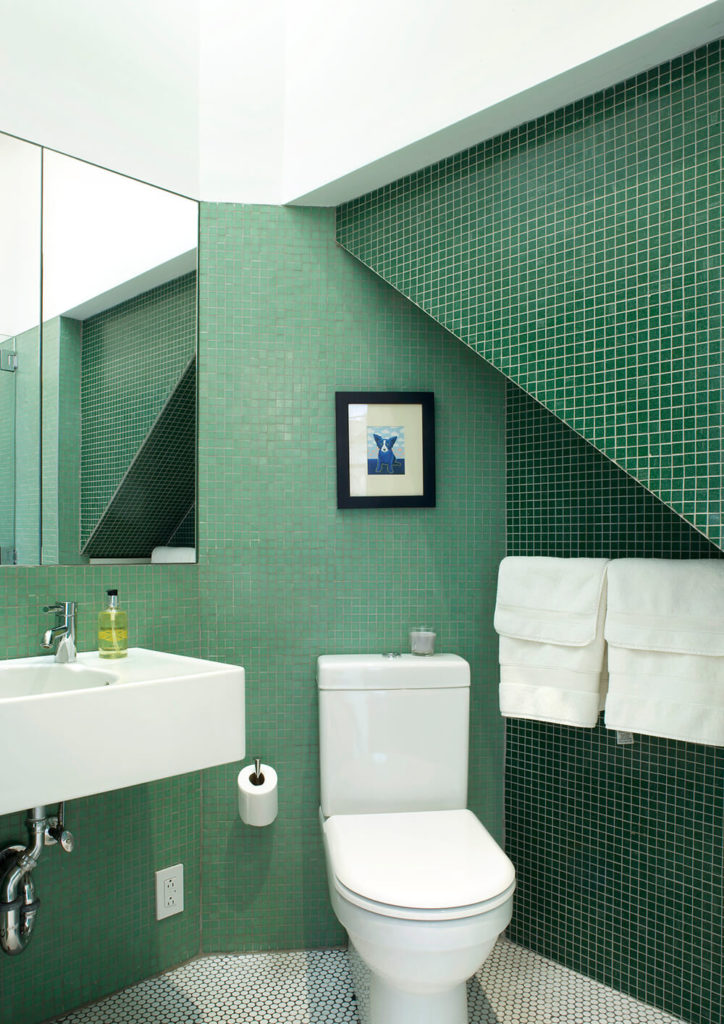 The guest bathroom is a study in color and done up in four different shades of green mosaic tiles to show off the angles created by the fire stairs that the bathroom is tucked under to fully utilize the space. White accents keep the room from feeling to dark or overwhelming.