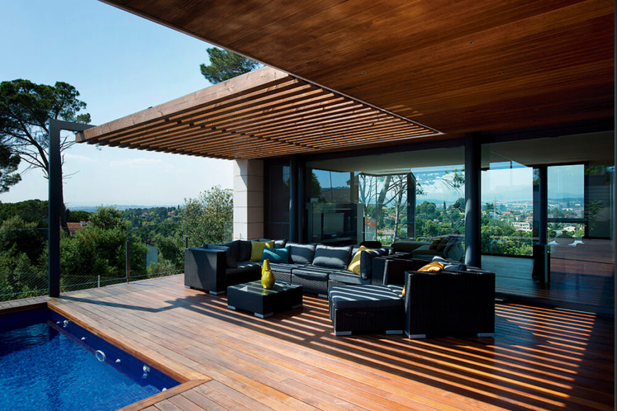 This patio is partially shaded by overhanging rafters. The black outdoor furniture is accented by bright colored pillows and decorative vases centered on the coffee table.