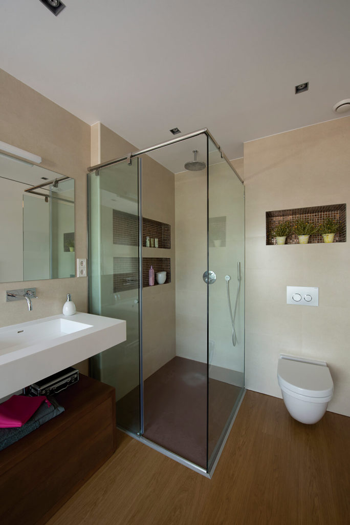 This angle reveals the shower in the bathroom, located in the corner of the room and surrounded by glass walls. Notice the rich wood floors and the contrast from dark floors to light walls.