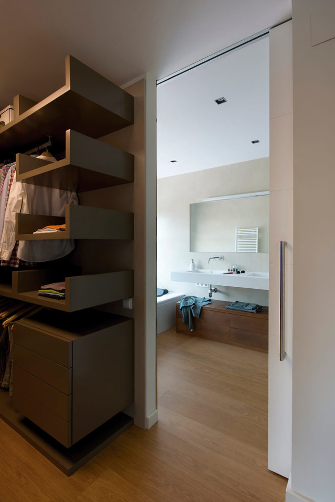 An offshoot from the bathroom leads into the closet space, which is not fully visible, but it is apparent that the closet is spacious and designed to accommodate the users with efficiency. The floor remains consistent with that of the bathroom while the shelving and drawers are a darker, sleek material.