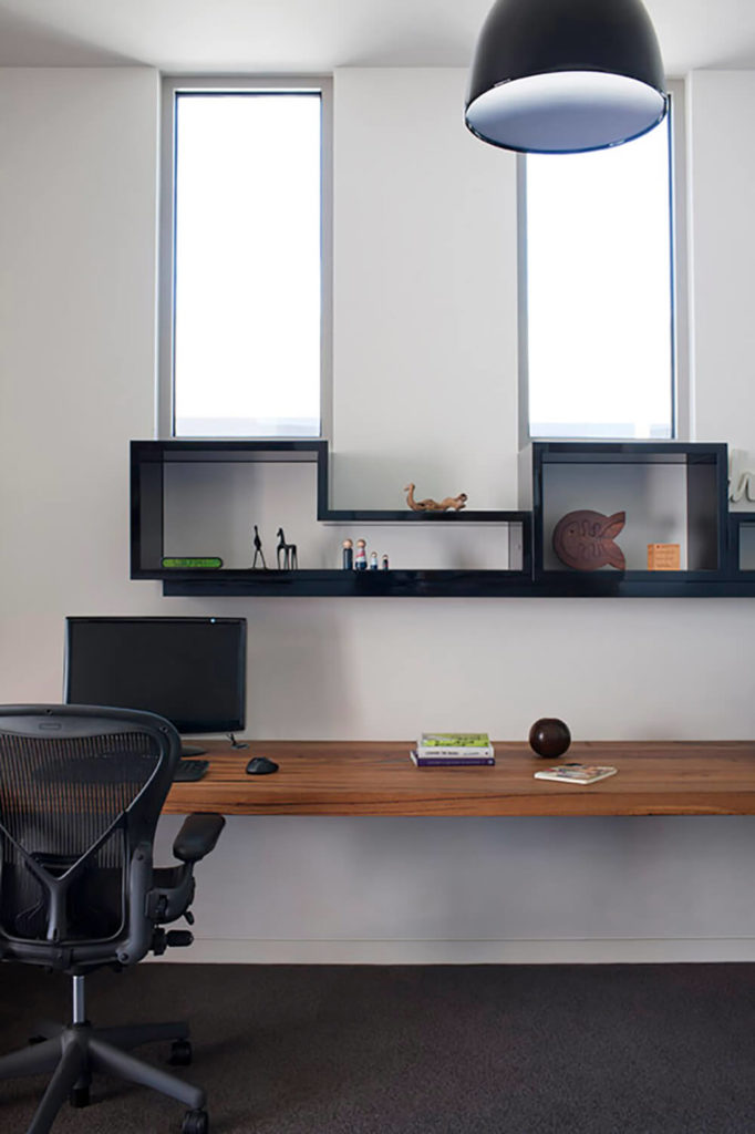 A floating desk was installed along the length of the outside wall. This offers plenty of work space without over crowding the room. The black floating shelves over the desk bring the modern design of the rest of the house into the room while also offering extra storage.