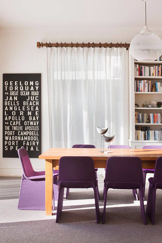 Royal purple chairs liven up the dining room, located just off the living room. The spherical pendant light brings a modern touch to the room to complement the decor of the surrounding space. Bold typographic wall art offsets the muted hues of the room while maintaining the design used in the rest of the house.