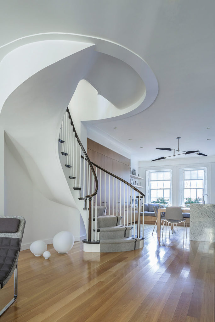 Just beyond the first welcoming area, the light hardwood floor continues on into a small kitchen/dining space. There is a mirrored bench and set of windows on this side, with a spiral staircase acting as a division line.