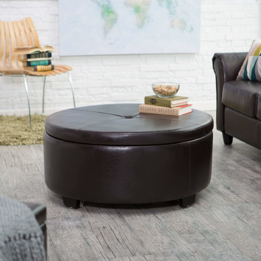 The Corbett ottoman is designed for a modern home, featuring luxurious craftsmanship and discreet storage. The piece is upholstered in bonded leather in a deep chocolate with burgundy overtones. The classic round shape makes it ideal as both an ottoman and as a coffee table. The leather surface makes cleaning the occasional spill a snap!