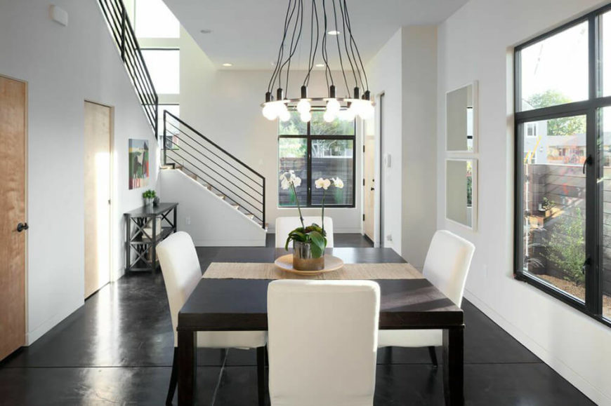 As you enter the home, you immediately walk into the dining area. Solid black floors contrast the white walls and dining chairs. Directly in front of the entrance, there is a staircase leading up to the second floor.