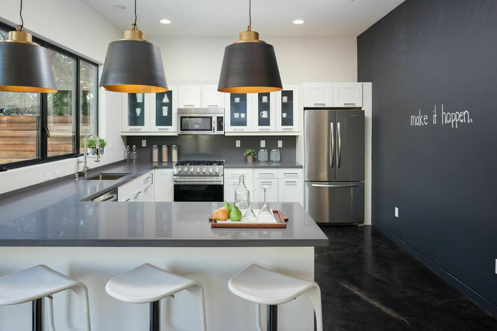 Stylish kitchen with a gray wall matching the counters' countertops. The pendant lights look stylish along with the dark-finished flooring.