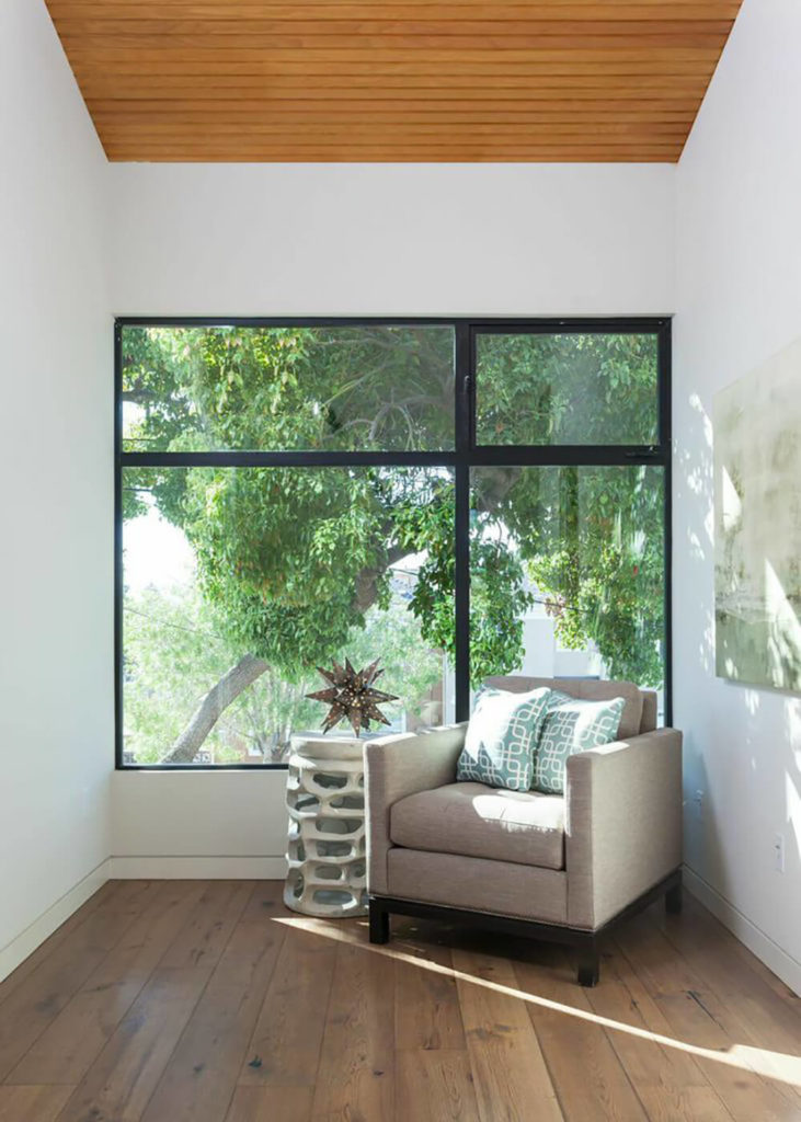 This lounging chair and decorative side table are set directly next to a large window, creating a space to sit and enjoy the sunlight from the interior of the home. The hardwood floors contribute to a calming atmosphere for this space.
