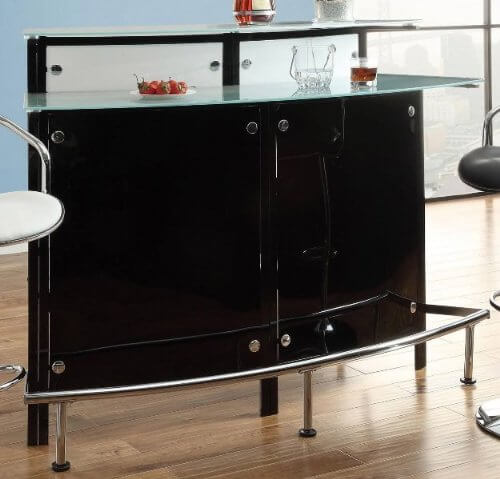 If your man cave leans toward the more elegant, modern end of style, this could be the perfect home bar setup. Glossy black cabinetry, chromed foot rails and hardware, and a tempered glass bar top make for a uniquely rich textural presence. The two-tiered bar makes for plenty of space to mix, pour, and serve drinks, while the glossy look will emphasize a sense of luxury in any modern man cave.