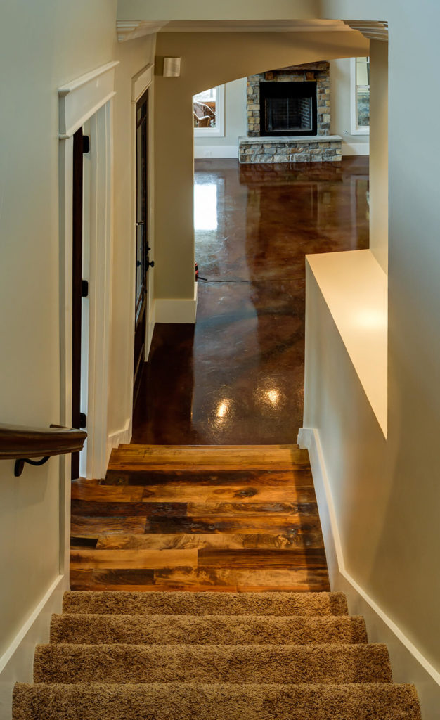 The view from the top of the stairs down into the rest of the house. This is the best angle to highlight the barn wood floor and the beautiful color striations seen in the floors of the rest of the house.