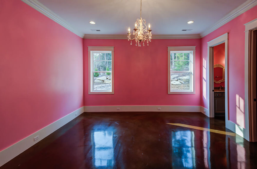 One of two guest bedrooms, the bright pink walls really work with the natural light to brighten up the room. The attached bathroom and walk-in closet can be seen along the right wall. This bedroom is located in the back corner of the first floor.