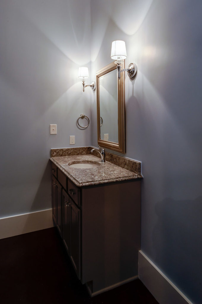 As with the other room, the same color is on the walls of the attached bathroom, brightening up the room considerably. The same contemporary light fixtures also highlight the mirror in this bathroom but a lighter cabinet keeps the room from feeling too small.