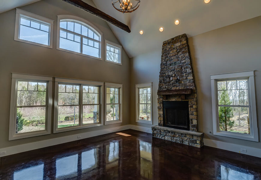 Windows line the walls of this massive room and allow plenty of light to come in, uninhibited. The rustic look of the stone adds to the overall design of the project when viewed with the exposed beams running across the ceiling and the reclaimed barn wood used throughout the home.