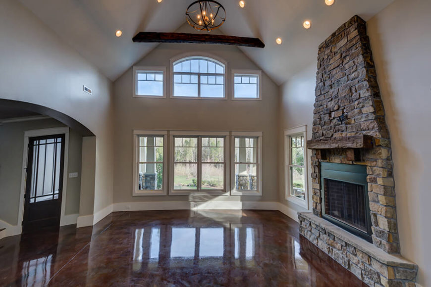 On the other side of the foyer is the great room. With two story vaulted ceilings and a beautiful stonework fireplace mantle, this room is one of the key features of the design. The color variations of the treated floors are more visible here, giving the floors more interest that just a flat concrete would.