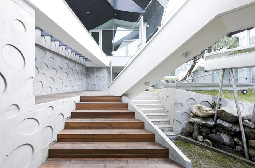 On the lowest level of the inner courtyard, we see the approach to the home interior via a series of overlapping stairs. The material variety here is astounding, with concrete, natural wood, steel, and boulders meeting lush green grass and the reflective glaze of windows.