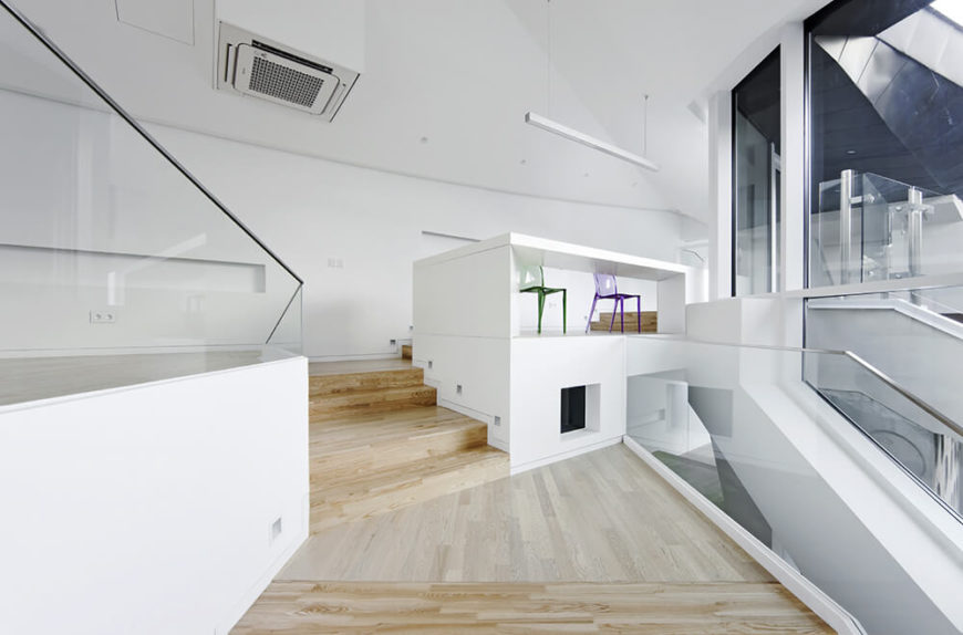 Through glass balustrades, we can see various layers of the home above and below this living room space. The prevalence of glass and open floor plans makes for a truly interconnected, yet layered, experience.