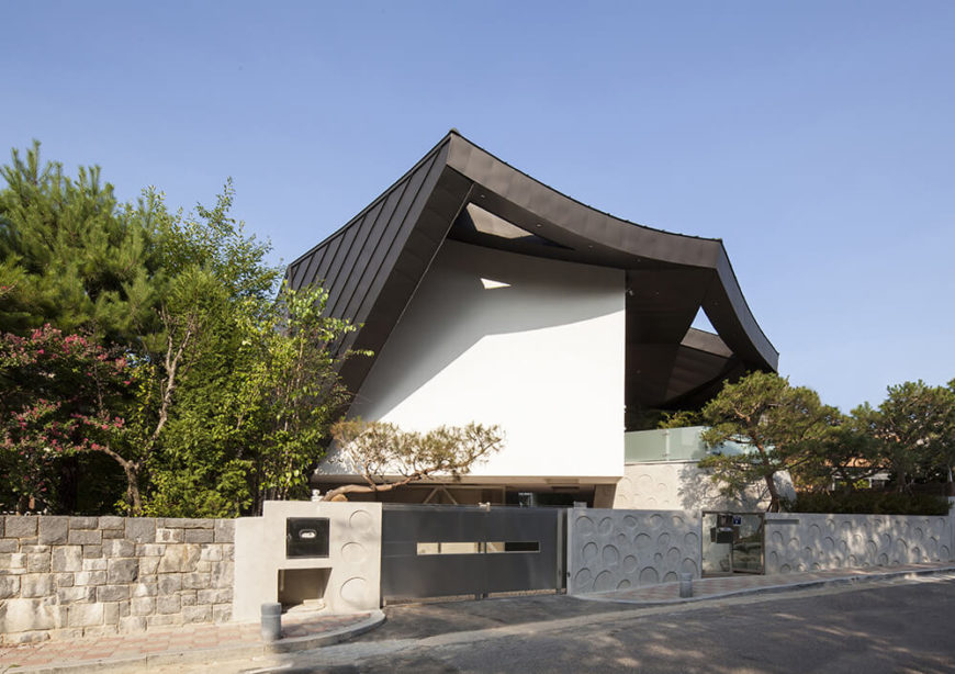 As seen from the street, the home is mostly buttoned up and private, with a low stone wall surrounding the property and the black roof structure soaring over the white building.