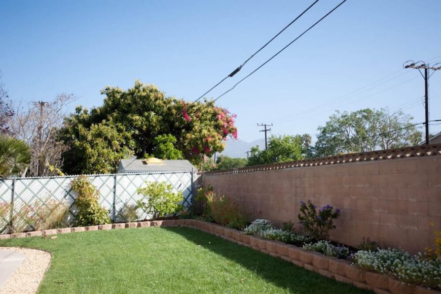 Here we see a great example of a yard that utilizes the low-cost chain link fence for the parts of the yard that aren't visible from the street. The front of of the home's fence is brick with a lattice border, while the rest is slatted chain link for more privacy. This is a perfect way to embrace the low cost option of chain link while keeping up the curb appeal!